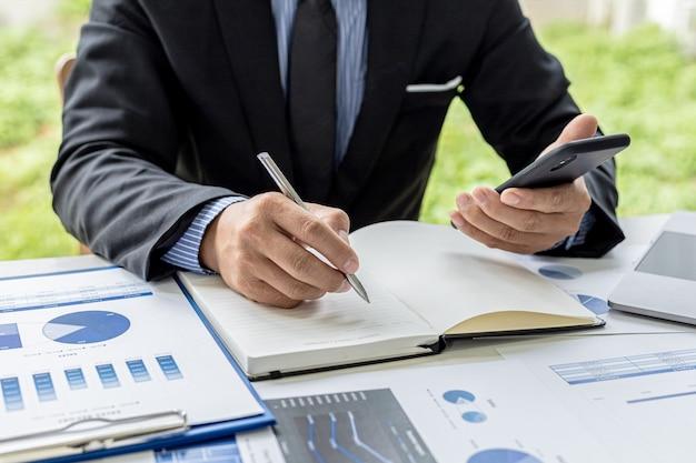 Бизнесмен делает записи со своего мобильного телефона в блокноте, он владеет компанией, проверяет финансовые документы компании в своем офисе. понятие финансового менеджмента.