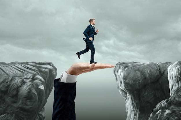 ビジネスマンは投資家の大きな手に沿って割れ目を横切って走ります。