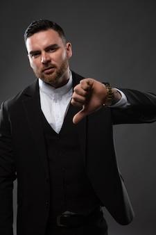 ビジネスマンは、指を下に向けてジェスチャーが悪いことを示しています。