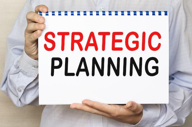 ビジネスマンは、白い背景にテキスト戦略計画のシートを表示します