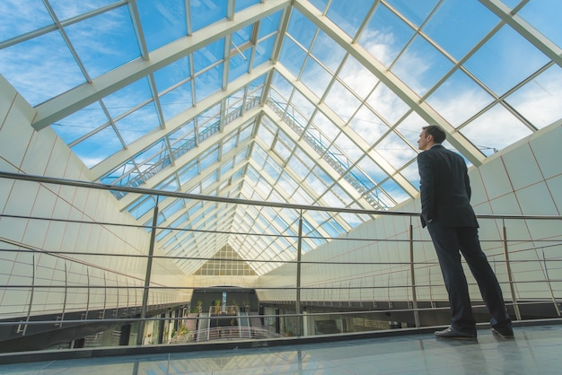 ビジネスマンは空の背景にオフィスのバルコニーに立っています