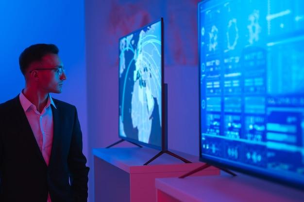 Бизнесмен, стоящий возле экранов в темной комнате