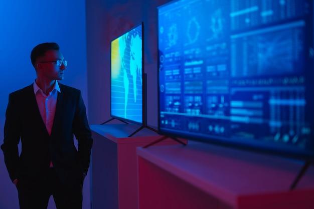 Бизнесмен, стоящий возле экранов с графиками