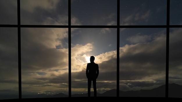 灰色の空の背景にパノラマの窓の近くに立っているビジネスマン