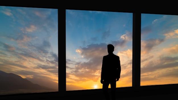 夕日の背景にパノラマの窓の近くに立っているビジネスマン