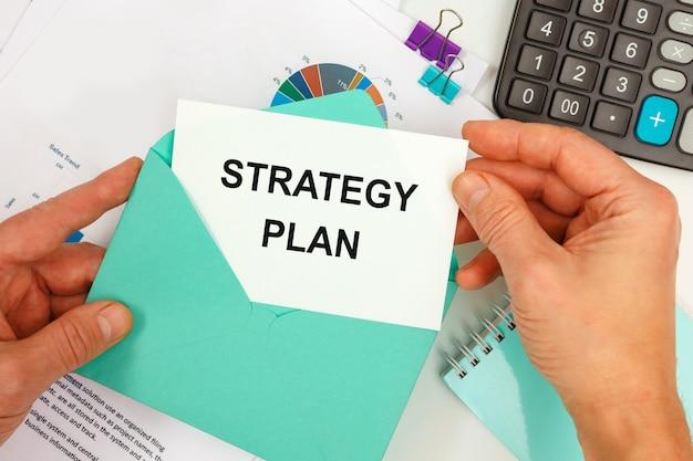 사업가는 사무실 책상 배경에 strategy plan이라는 텍스트가있는 봉투에서 카드를 꺼냅니다.