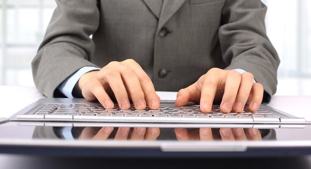Бизнесмен, печатающий на своем ноутбуке в офисе