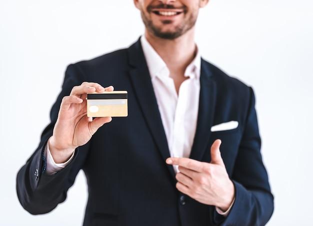 白い背景の上に立っているクレジットカードを持つビジネスマン