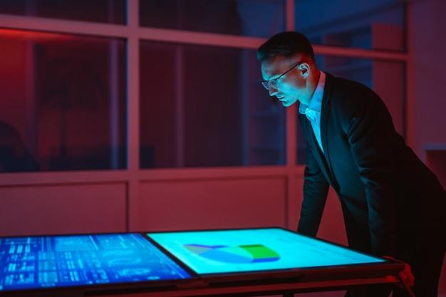 Бизнесмен, работающий с большими дисплеями в темной комнате