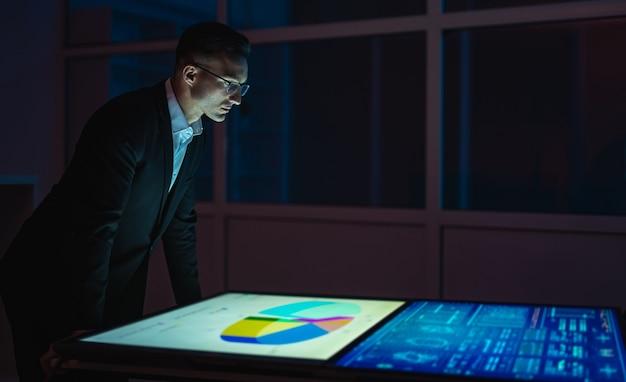 Бизнесмен, работающий с большими экранами в темной комнате