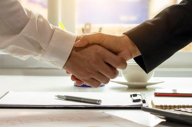 一緒にチームワークのパートナーになる契約が結ばれた後、ビジネスマンは会議と幸せなビジネスマンの握手を終えました。