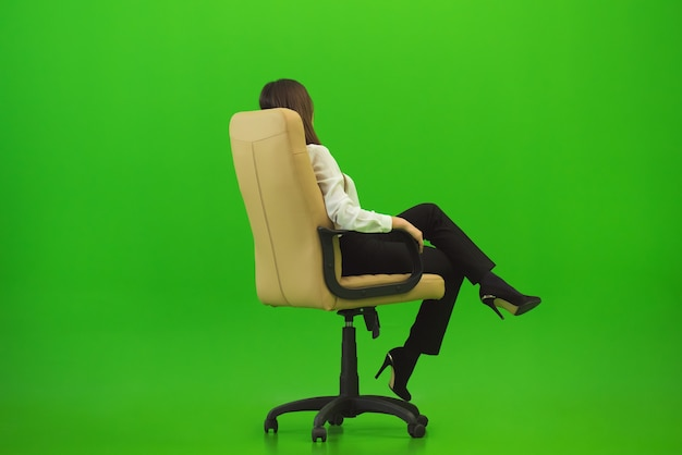 녹색 배경의 의자에 앉아 있는 사업가