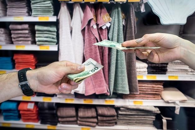 Покупатель покупает полотенца для дома и отдает продавцу доллары. концепция покупок