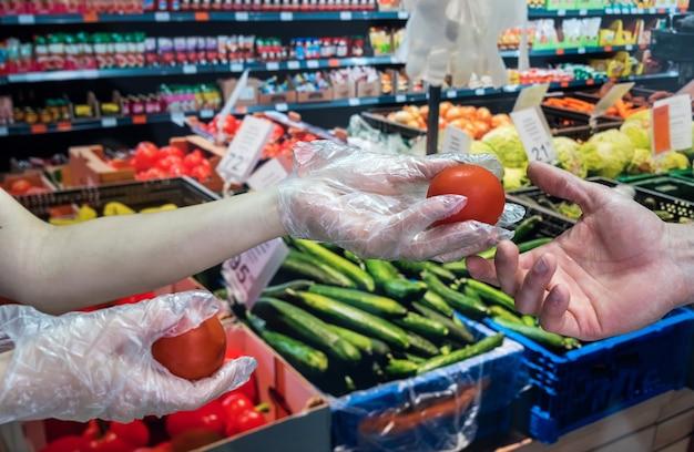 手袋をはめたバイヤーは、パンデミック時に野菜を選びます Premium写真