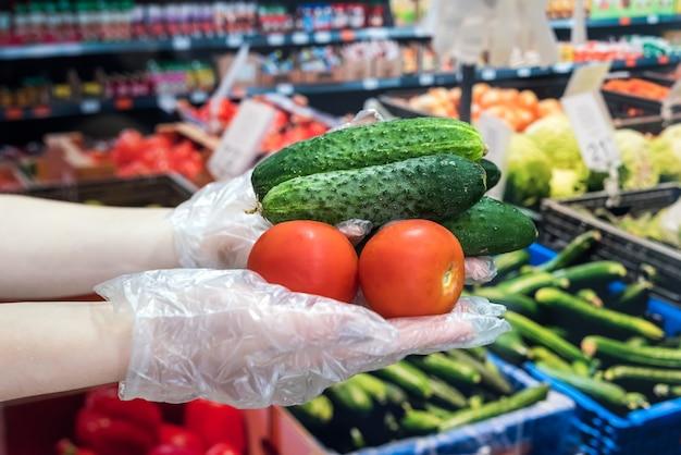 Покупатель в перчатках выбирает овощи в супермаркете