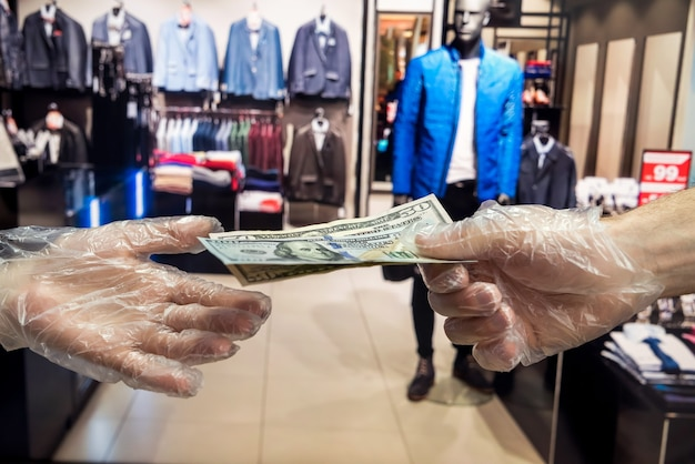 플라스틱 장갑을 착용 한 구매자는 옷가게에있는 상품에 대해 구매자에게 달러를 제공합니다. 위생 개념. 새로운 위험한 바이러스로 인한 대유행. 코로나 바이러스
