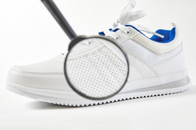 Покупатель ищет в обуви дефекты и макродетали с лупой. стиль и мода кроссовок. открытие дышащей обуви в дыре.