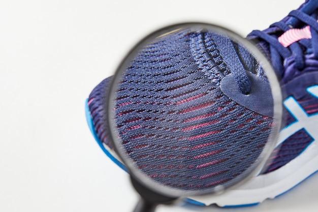 Покупатель ищет в обуви дефекты и макродетали с лупой. стиль и мода кроссовок. открытие дышащей обуви.