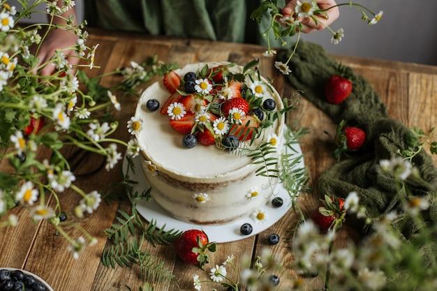 케이크는 딸기와 꽃으로 장식되어 있습니다.