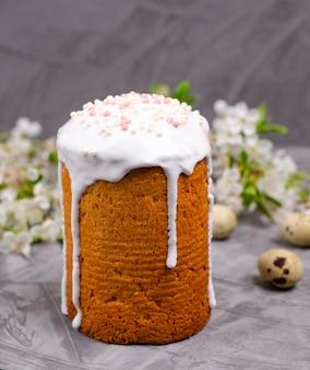 Торт декорирован белой сахарной глазурью и сдобрен на темном фоне.