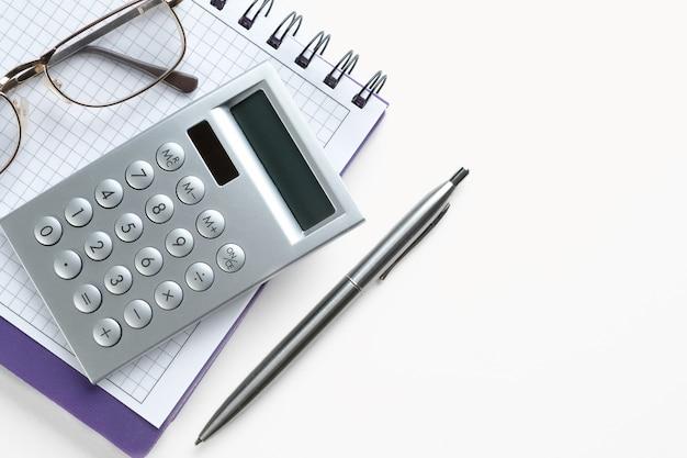 Калькулятор и очки на открытом блокноте. рядом с ручкой. чистый лист блокнота с записями бизнесмена или бухгалтера. концепция финансовой отчетности.