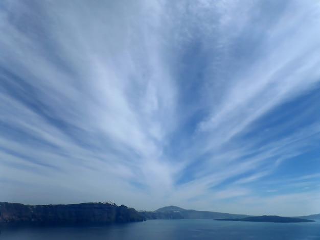 Кальдера среди голубого облачного неба и голубого спокойного моря, остров санторини, греция
