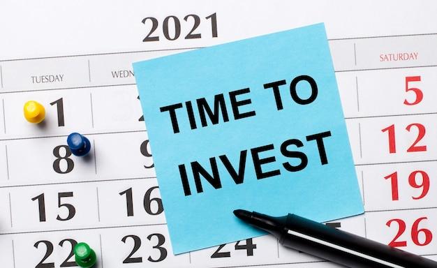 На календаре есть синяя наклейка с надписью «время инвестировать» и черный маркер. организационная концепция. вид сверху