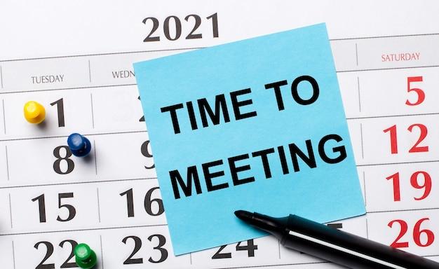 На календаре есть синяя наклейка с надписью «время до встречи» и черный маркер. организационная концепция. вид сверху