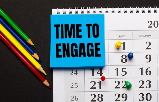 В календаре есть светло-голубая бумага для заметок с надписью «время задержать». рядом цветные карандаши на темном фоне