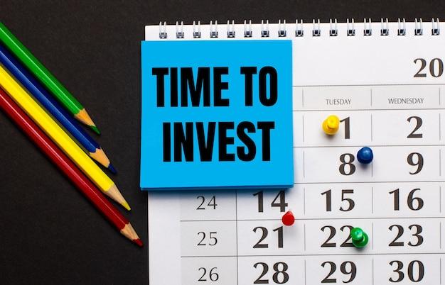 В календаре есть голубая бумага для заметок с надписью «время инвестировать». рядом цветные карандаши на темном фоне. вид сверху