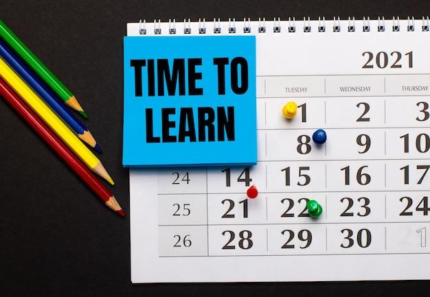 В календаре есть голубая бумага для заметок с текстом «время учиться». рядом цветные карандаши на темной поверхности