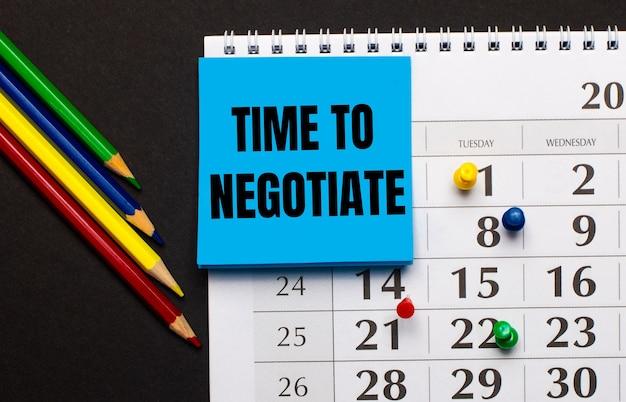 カレンダーには、「交渉する時間」というテキストが書かれた水色のメモ用紙があります。暗い表面にある近くの色鉛筆。上から見る