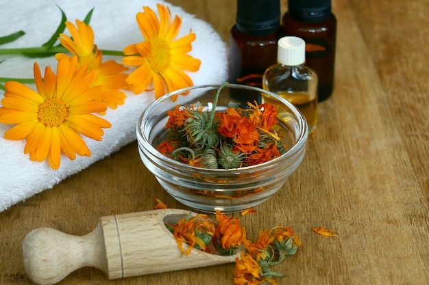 Экстракт календулы. лекарственные растения. бутылки и сушеные лепестки календулы лекарственной с мацерированным маслом на деревянном столе.