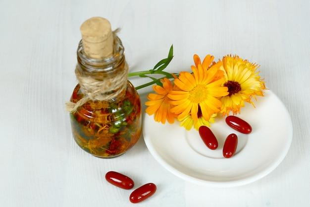 Экстракт календулы. лекарственные растения. бутылки и сушеные календулы. цветок апельсина