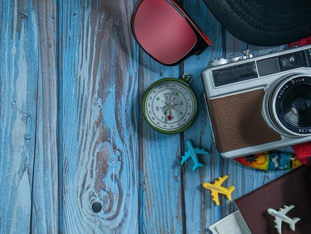 여행 컨셉을 위해 나무 탁자에 있는 카메라와 여권.