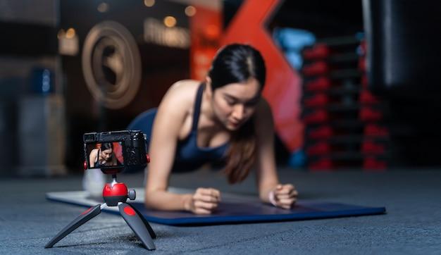 三脚のカメラが写真やビデオを撮っています。良い形のアジアの女性トレーナー板のポーズのサンプルを教えたり、実行したりすることは、オンライントレーニングコンセプトの体重トレーニングです。