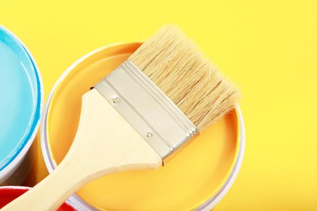 Банки с краской для внутренних стен размещаются на желтом фоне.
