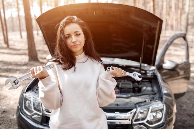 Машина сломалась. авария на дороге. женщина открывает капот и проверяет двигатель и другие детали автомобиля.