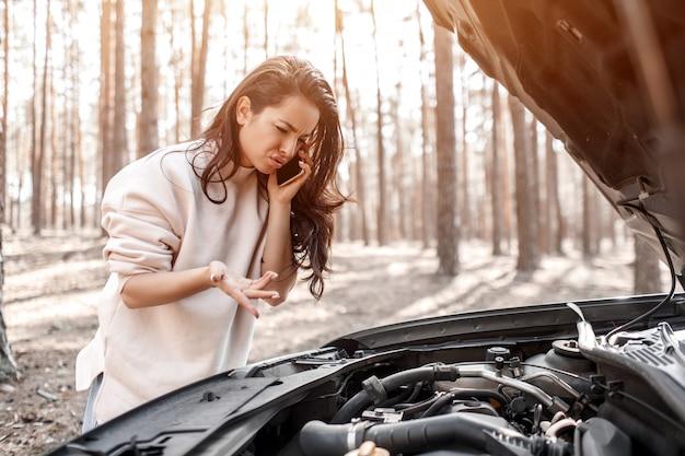 Машина сломалась. женщина открывает капот и проверяет двигатель и другие детали автомобиля.