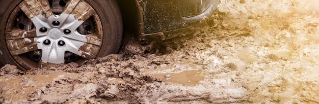 車は泥の中の未舗装の道路で動けなくなった