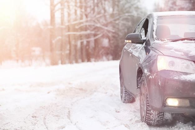 Автомобиль серый на дороге в лесу. поездка за город на зимние выходные. машина на дороге перед зимним парком.