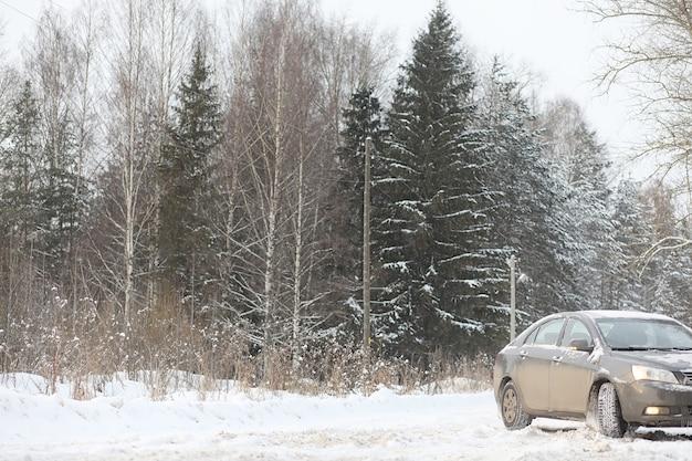 車は森の中の道で灰色です。冬の週末の田舎への旅行。ウィンターパーク前の道路を走る車。