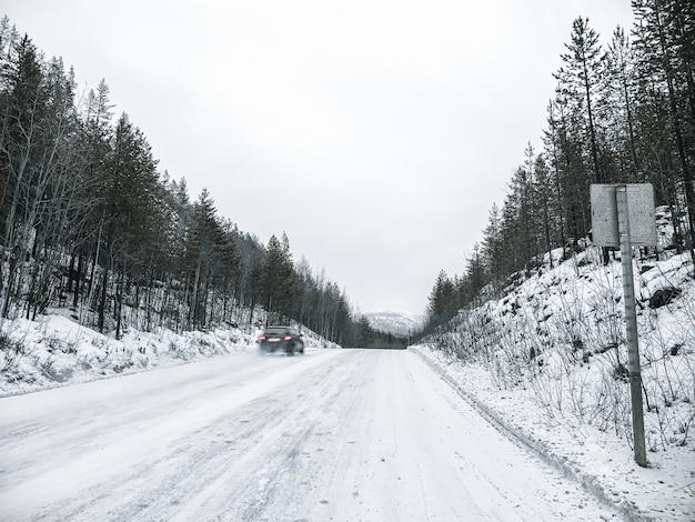 차가 움직이고 있습니다. 미끄러운 가파른 오르막길. 미끄러운 겨울 길