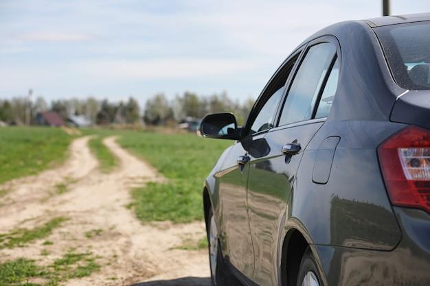 Автомобиль припаркован в поле. машина едет по проселочной дороге к дому. автомобиль серый на лугу перед проселочной дорогой