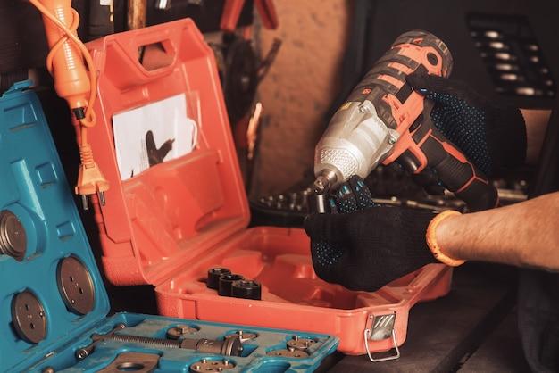 Автомеханик держит в руке пневматический ключ для ремонта автомобиля. инструментальный бокс