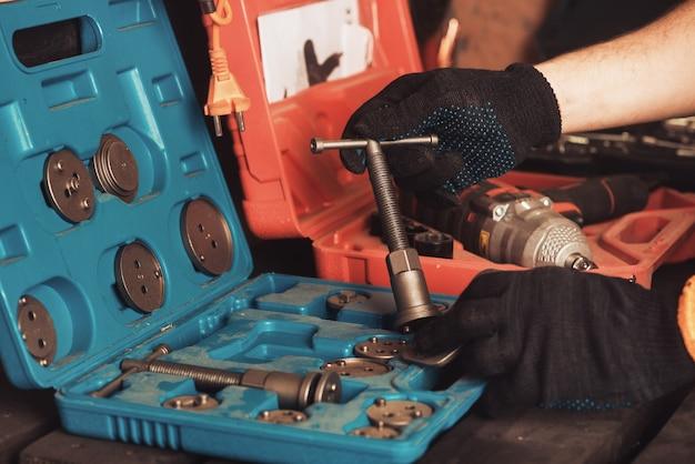 Автомеханик держит в руке специальный ключ для ремонта автомобиля. инструментальный бокс.