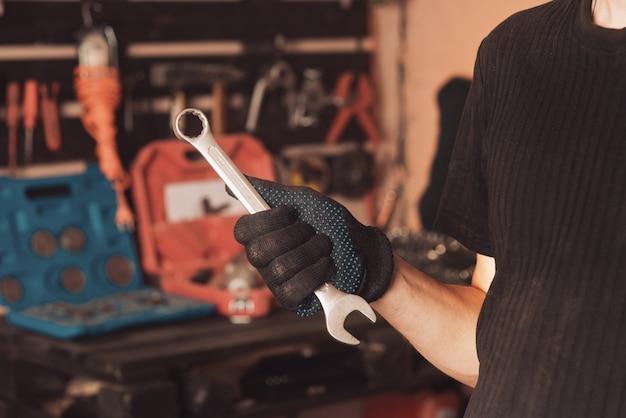 자동차 정비사는 자동차 수리 도구가 있는 보드 배경에 렌치와 통로를 손에 들고 있습니다. 확대. 자동차 수리 차고