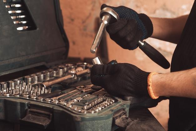 자동차 정비사는 자동차 수리 도구가 있는 보드 배경에 렌치와 통로를 손에 들고 있습니다.
