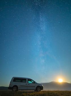 天の川を背景にした車。夜の時間
