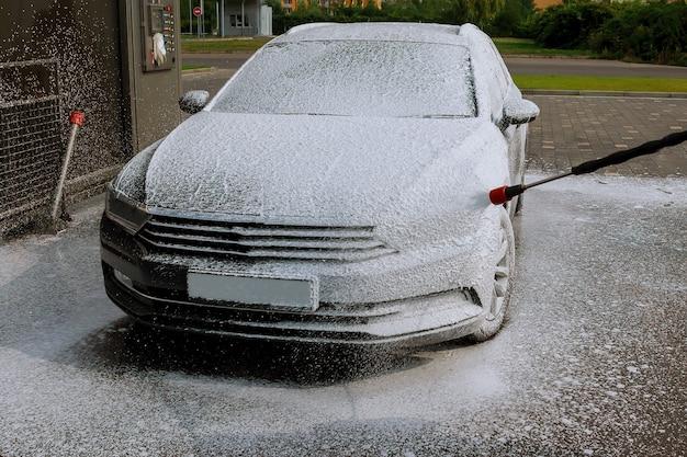 車の所有者は、セルフサービスの洗車を泡で洗車します